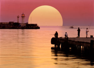 UKRAINE - YALTA. A beautiful red sunset in the sea port. Sun dominates the horizon. Lighthouse orientates vessels in the Black Sea. Local fishermen are fishing on a pier.